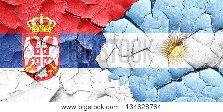 Serbia flag with Argentine flag on a grunge cracked wall