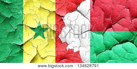 Senegal flag with Madagascar flag on a grunge cracked wall