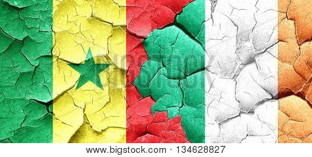 Senegal flag with Ireland flag on a grunge cracked wall