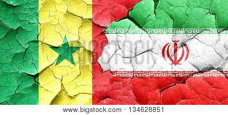 Senegal flag with Iran flag on a grunge cracked wall