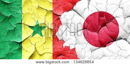 Senegal flag with Japan flag on a grunge cracked wall