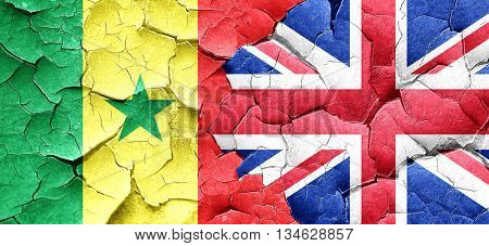 Senegal flag with Great Britain flag on a grunge cracked wall