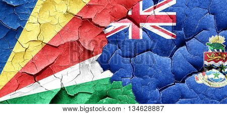 seychelles flag with Cayman islands flag on a grunge cracked wal