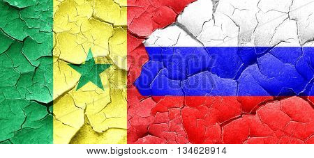 Senegal flag with Russia flag on a grunge cracked wall
