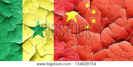 Senegal flag with China flag on a grunge cracked wall