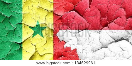 Senegal flag with Indonesia flag on a grunge cracked wall