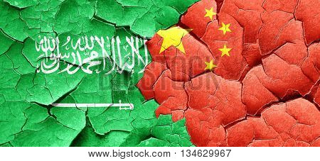 Saudi Arabia flag with China flag on a grunge cracked wall