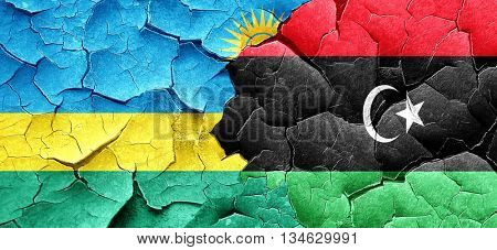 Rwanda flag with Libya flag on a grunge cracked wall