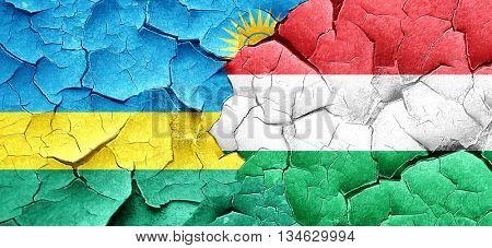 Rwanda flag with Hungary flag on a grunge cracked wall