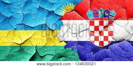 Rwanda flag with Croatia flag on a grunge cracked wall