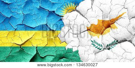 Rwanda flag with Cyprus flag on a grunge cracked wall