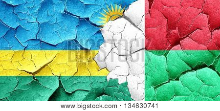 Rwanda flag with Madagascar flag on a grunge cracked wall
