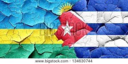 Rwanda flag with cuba flag on a grunge cracked wall