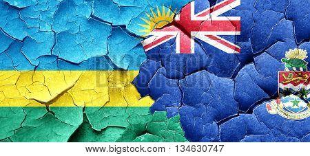 Rwanda flag with Cayman islands flag on a grunge cracked wall