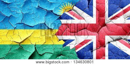 Rwanda flag with Great Britain flag on a grunge cracked wall
