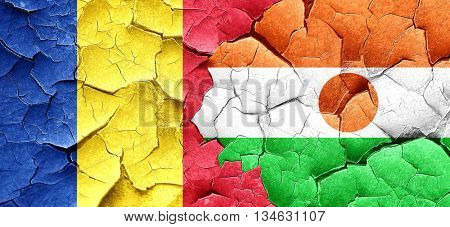 Romania flag with Niger flag on a grunge cracked wall