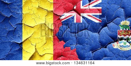 Romania flag with Cayman islands flag on a grunge cracked wall