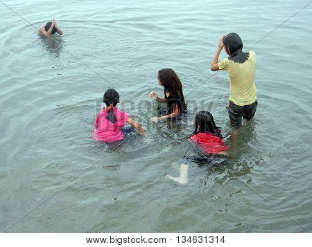 CEBU CITY, CEBU / PHILIPPINES - JULY 30, 2011: Children play in the water at a public beach in Cebu.