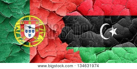 Portugal flag with Libya flag on a grunge cracked wall