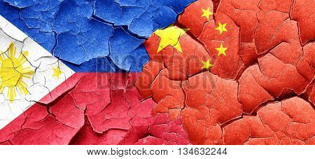 Philippines flag with China flag on a grunge cracked wall