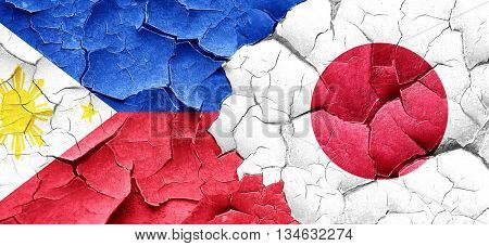 Philippines flag with Japan flag on a grunge cracked wall