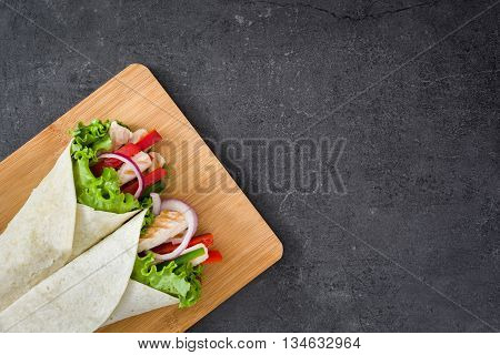 Mexican chicken fajitas with peppers lettuce and onion on slate background