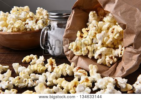 Closeup of a bag of fresh popped popcorn with a bow and salt shaker.