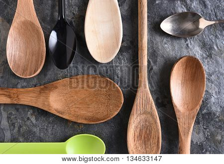 An assortment of wood, plastic, and metal spoons on a slate surface. Top view in horizontal format.