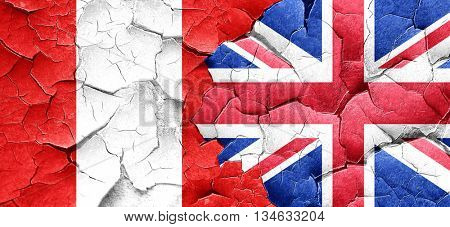 Peru flag with Great Britain flag on a grunge cracked wall