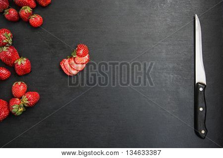 One sliced strawberry among other whole on black table