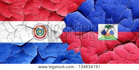 Paraguay flag with Haiti flag on a grunge cracked wall