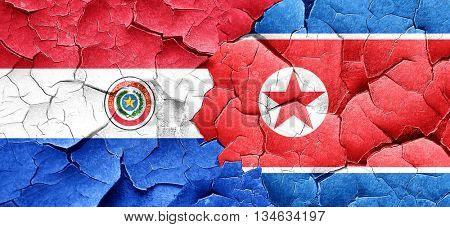 Paraguay flag with North Korea flag on a grunge cracked wall