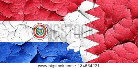 Paraguay flag with Bahrain flag on a grunge cracked wall