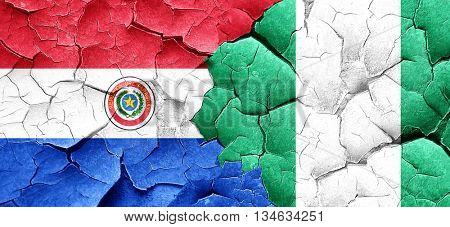 Paraguay flag with Nigeria flag on a grunge cracked wall