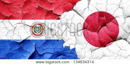 Paraguay flag with Japan flag on a grunge cracked wall
