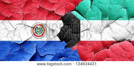 Paraguay flag with Kuwait flag on a grunge cracked wall