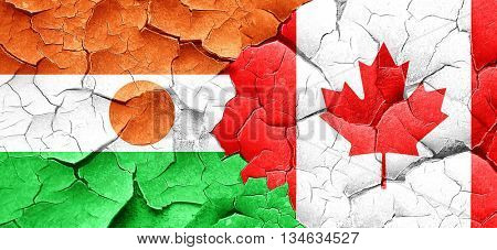 niger flag with Canada flag on a grunge cracked wall