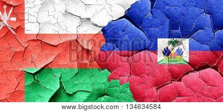Oman flag with Haiti flag on a grunge cracked wall