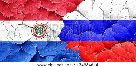 Paraguay flag with Russia flag on a grunge cracked wall