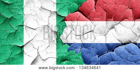 Nigeria flag with Netherlands flag on a grunge cracked wall