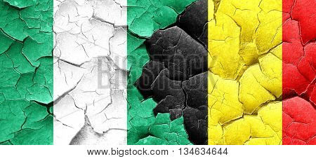Nigeria flag with Belgium flag on a grunge cracked wall