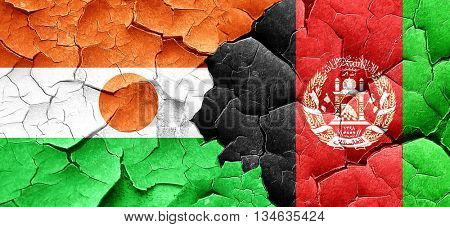 niger flag with afghanistan flag on a grunge cracked wall