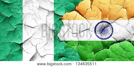 Nigeria flag with India flag on a grunge cracked wall