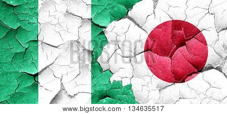 Nigeria flag with Japan flag on a grunge cracked wall