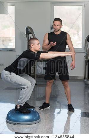 Personal Trainer Helping Man On Bosu Balance Ball