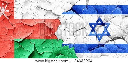 Oman flag with Israel flag on a grunge cracked wall