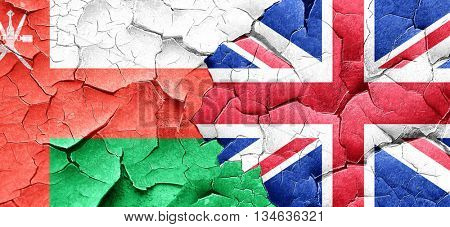 Oman flag with Great Britain flag on a grunge cracked wall