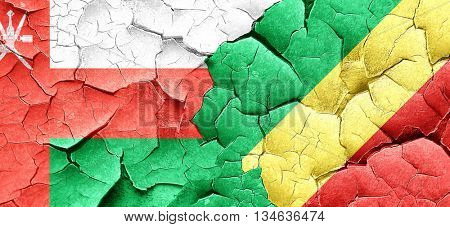 Oman flag with congo flag on a grunge cracked wall