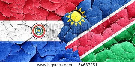Paraguay flag with Namibia flag on a grunge cracked wall