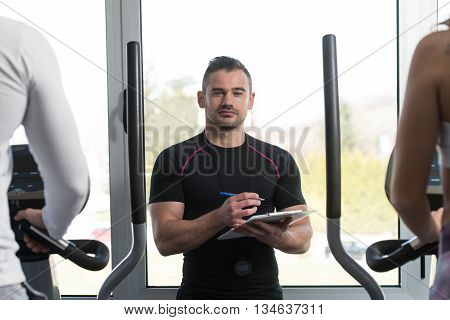Trainer With Clipboard Monitors People While They Running